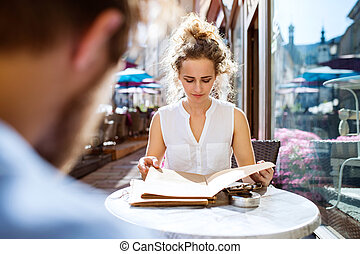 Young woman sitting in a cafe. - Beautiful young woman with...