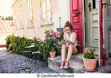 Young woman with a smartphone at the doorstep. - Young woman...