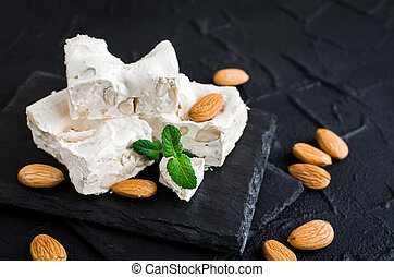 Sweet nougat with almonds on black stone board on concrete...