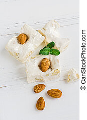 Sweet nougat with almonds on white wooden background. Pieces...