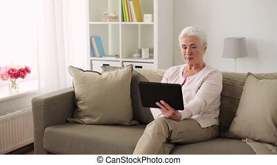 old woman with tablet pc having video chat at home -...