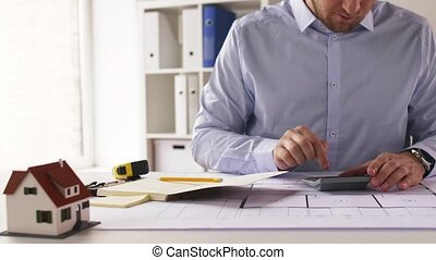 architect with blueprint counting on calculator -...