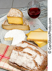Different french cheeses with a glass of wine - Different...