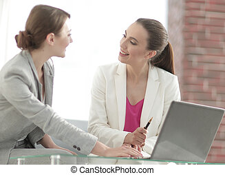 two successful business women discussing current issues -...