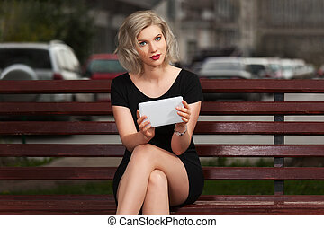 Young fashion blond woman with tablet computer sitting on...