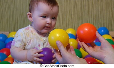 baby playing with plastic balls - small baby make choice of...