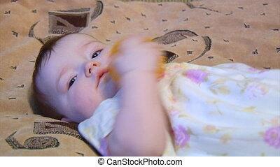 little baby - close-up small baby laying down with yellow...