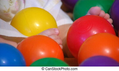 baby playing with plastic balls - close-up feet of small...
