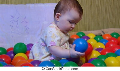 baby playing with plastic balls 2 - small baby playing among...