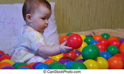 baby playing with plastic balls 1 - small baby playing among...