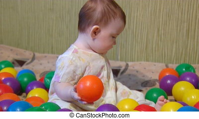 baby playing with plastic balls - small baby playing among...