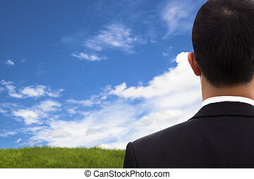 View of Businessman's back and watching blue sky and green...