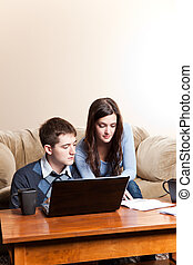 Couple paying bills by online banking - A couple paying...