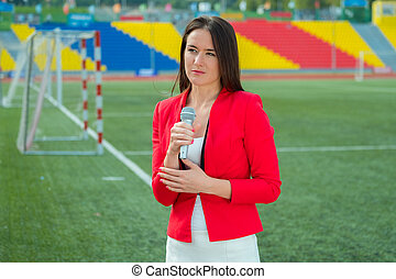 Young girl TV reporter is broadcasting from stadium