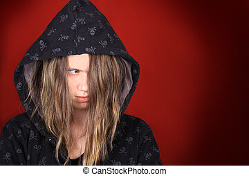 Troubled teenager with hooded sweater on a red background