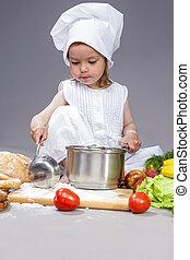 Portrait of Caucasian Little Girl In Cook Uniform Working...