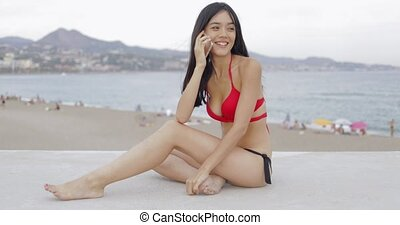 Charming girl talking phone on beach - Fit young model in...