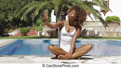 Pretty girl taking selfie in pool - Young charming ethnic...