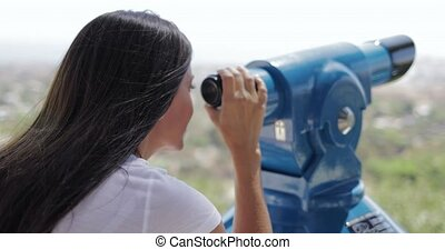 Woman using spyglass on city viewpoint - Anonymous brunette...