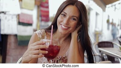 Smiling woman posing with drink in cafe - Portrait of...