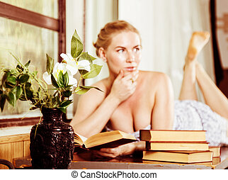 young woman reads a book lying on a desk in front of a...