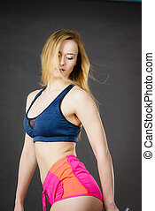 Fit woman wearing sports clothing bra and pink shorts....
