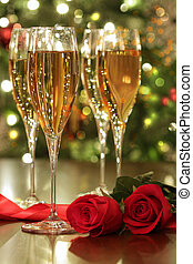 Glasses of champagne and red roses with festive background