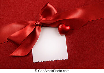 Satin bow and white card for gift on red