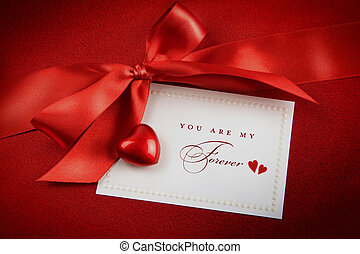 Red bow and white card for gift on  satin background