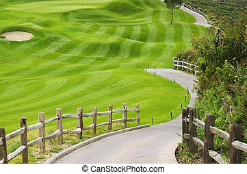 Picteresque green golf field with a wooden fence