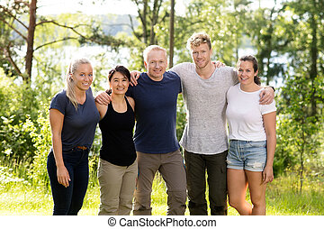 Confident Friends Standing Arms Around In Forest - Portrait...