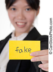 "fake - ""Fake"" on business card holding by Asian..."