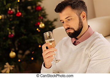 Upset man drinking champagne alone on Christmas Eve -...