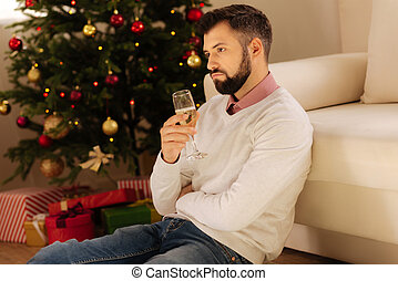 Upset man sitting on floor and drinking champagne - Lonely...