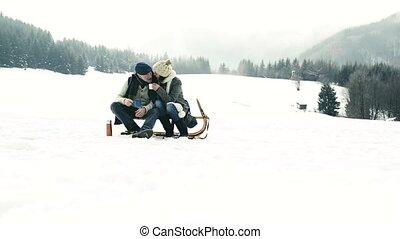 Beautiful senior couple on sledge drinking tea, winter day....