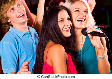 Singing - Photo of pretty girls with microphone singing in...