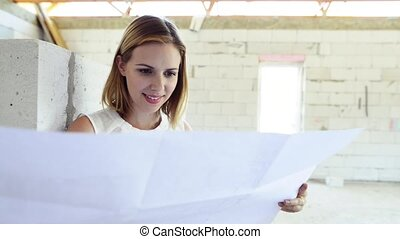 Young woman at the construction site. Woman looking at plans...