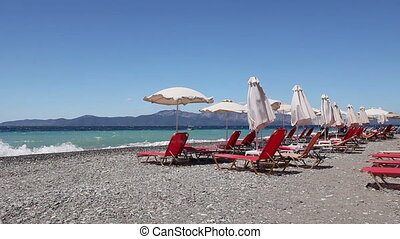 Umbrellas with loungers placed next to the coastline -...
