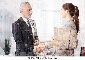 Positive professional colleagues having a firm handshake -...