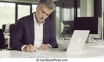 Mature businessman in black suit in the office working. -...