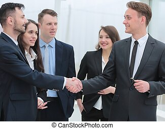 business team looks at the handshake business partners -...
