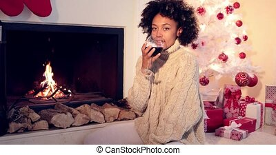 Pretty woman holds wine glass beside fireplace - Pretty...