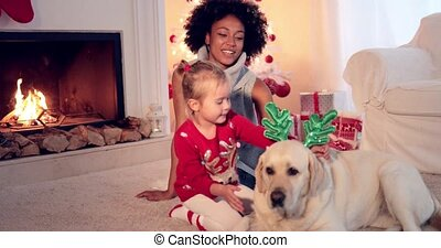 Mom and daughter in sweaters play with pet dog - Mom and...