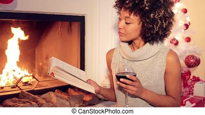 Young woman relaxing with a book and red wine at Christmas...