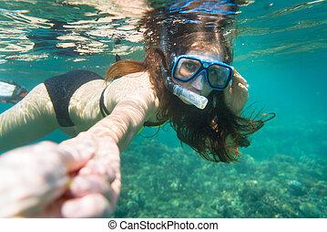 Snorkelling woman makes tempting gesture in ocean -...
