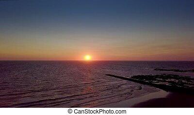 Sun rising above ocean water - Aerial shot of breathtaking...