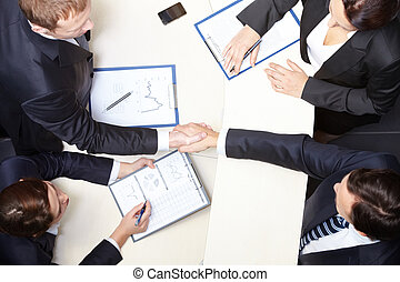 Agreement - Above view of business partners handshaking...