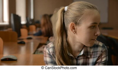Cheerful young blonde with hands on chin. Female student in...