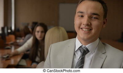 Portrait of a young man in a suit and tie smiling. Students...