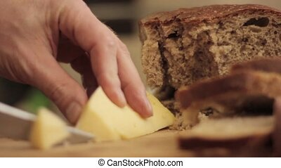 Cutting cheese on a wooden board. Close-up man hand with knife